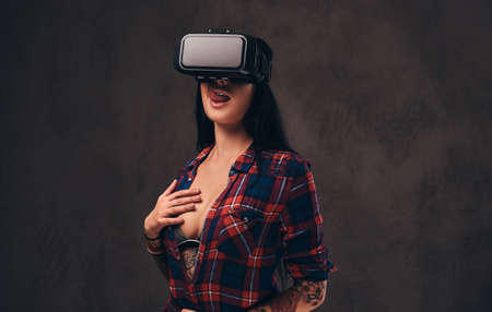 Photo pour Tattooed girl wearing a red unbuttoned checked shirt wearing a VR headset. - image libre de droit