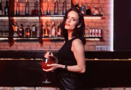 Foto de A beautiful girl wearing elegant clothes holding a cocktail while standing next to the bar counter - Imagen libre de derechos