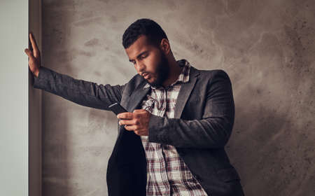 African-American guy using a phone in a studio.