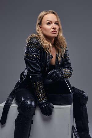 Foto de Portrait of a confident biker girl wearing racer costume sitting on a gray box in a studio. - Imagen libre de derechos