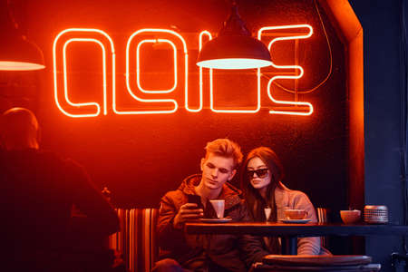 Foto de Trendy dressed young stylish couple sitting in a cafe with the industrial interior, chatting with friends or watching something on a phone - Imagen libre de derechos