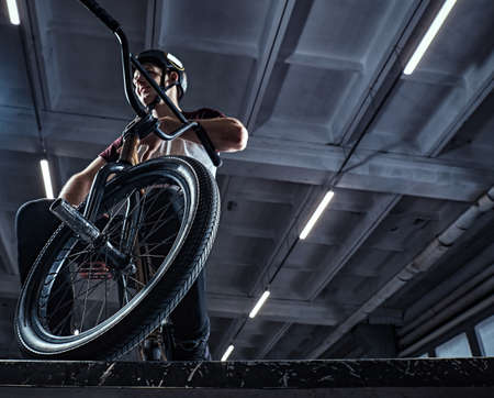 Professional BMX rider in protective helmet sitting on his bicycle in a skatepark indoors
