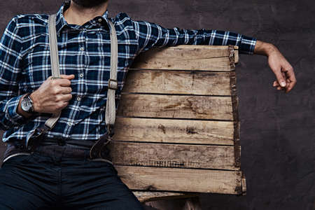 Photo for Old-fashioned man wearing a checkered shirt with suspenders sitting on a wooden scaffolding - Royalty Free Image