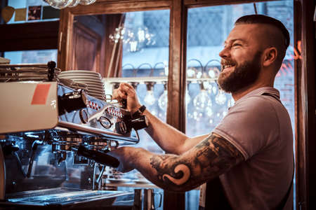 Foto per Cheerful barista with stylish beard and hairstyle making coffee for a customer in the coffee shop - Immagine Royalty Free