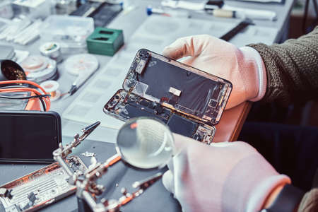 Foto de The technician carefully examines the integrity of the internal elements of the smartphone in a modern repair shop - Imagen libre de derechos