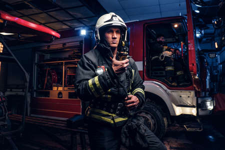 Photo pour The fire brigade arrived at the night-time. Fireman in a protective uniform standing next to a fire truck and talking on the radio - image libre de droit
