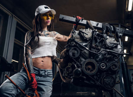 Foto de Sexual tattoed girl wearing cap and dirty clothes posing next to a car engine suspended on a hydraulic hoist in the workshop - Imagen libre de derechos