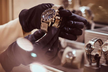 Foto de Close-up of the seller's hands in gloves shows the exclusive men's watch from the new collection in the luxury jewelry store - Imagen libre de derechos