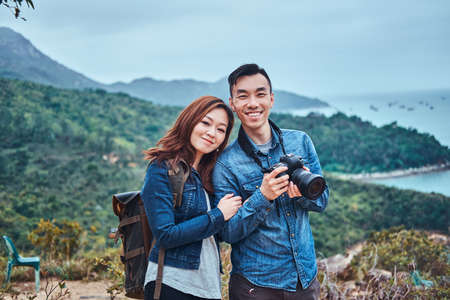 Photo for Cute romantic chinese couple enjoying beautiful nature. Man has a photo camera. They have denim shirts and casual style. - Royalty Free Image