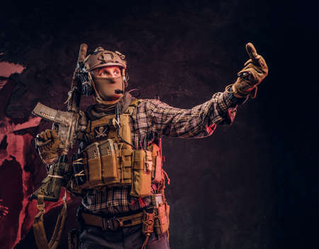 Foto für Special forces soldier in camouflage uniform posing with assault rifle, looks sideways and shows the middle finger. Studio photo against a dark textured wall - Lizenzfreies Bild