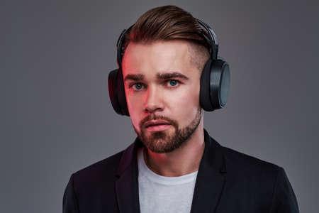 Foto de Young pensive man in wireless headphones is listening trendy music. - Imagen libre de derechos