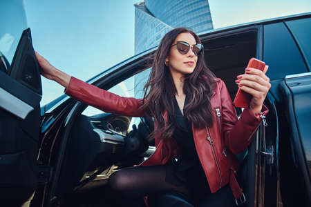 Foto de Beautiful smart women is posing in her new car while chatting on mobile phone. She is wearing red leather jacket and sunglasses. - Imagen libre de derechos