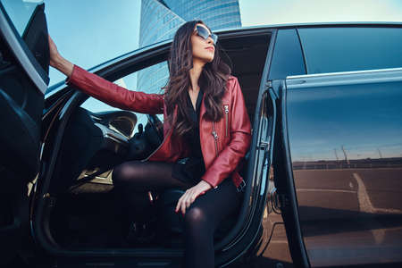 Photo pour Young attractive women is posing in her new car. She is wearing red jacket and sunglasses. - image libre de droit