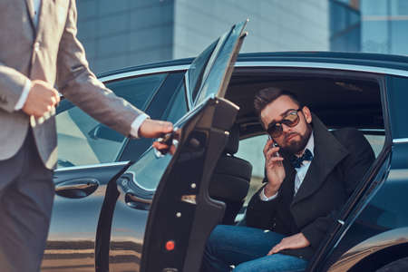 Attractive groomed man in sunglasses is talking by smartphone and sitting in the car while his assistant is opening door for him.