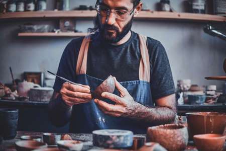 Photo pour Diligent entusiastic master in glasses at his  pottery studio is workig for a new dish. - image libre de droit