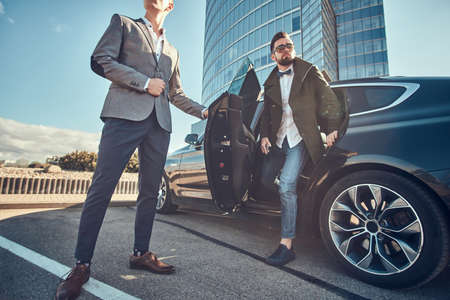 Smart serious businessman is going out from car while his assistant is opening door for him.