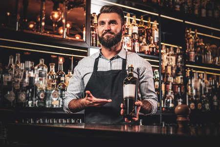 Foto de Happy smiling barman is offering special rare wine for customers at his cozy bar. - Imagen libre de derechos