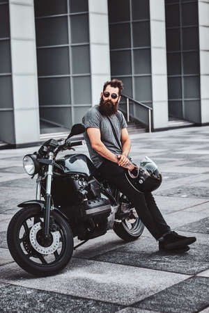 Photo pour Brutal tattooed biker in sunglasses is resting next to his motorbike in the city centre. - image libre de droit