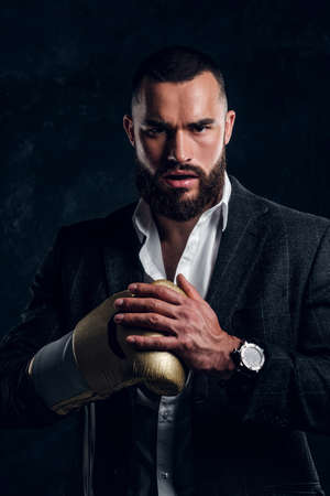 Photo pour Serious brutal man in suit and golden boxing glove is posing for photographer at dark photo studio. - image libre de droit
