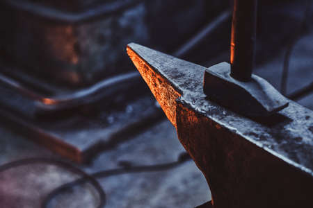 Foto de Close up photo shoot of hammer and anvil at dark smith workshop. - Imagen libre de derechos
