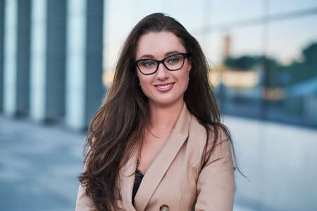Photo pour Portrait of a successful businesswoman with a charming smile posing on the street with interesting architecture at the background. - image libre de droit