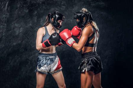 Foto de Process of fight between two female boxers in gloves and helmets over dark background. - Imagen libre de derechos