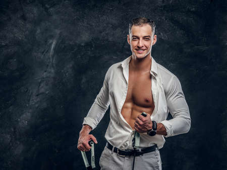 Photo pour Happy smiling man in white shirt is showing his perfect six pack when opened shirt. - image libre de droit