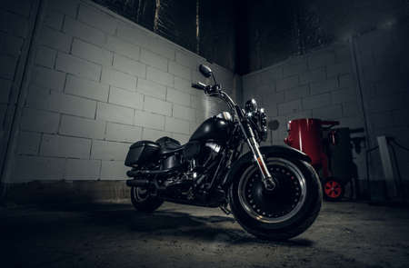 Photo for Beautiful shiny bike is parked in dark garage with white walls. - Royalty Free Image