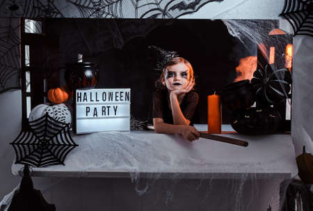 Photo for Little witch invite her friends for a party, she is sitting in well decorated area, there are spider web, pumpkins and broom. - Royalty Free Image