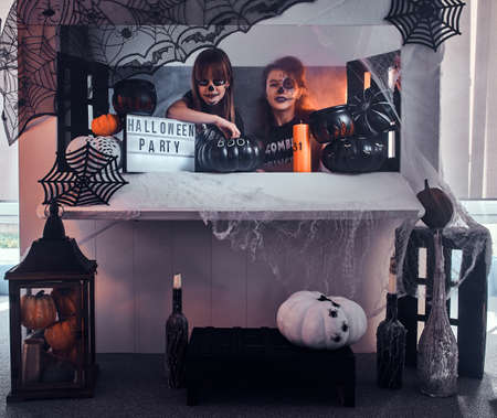 Photo pour Two pensive girls with scary makeup are sitting next to traditionally decorated table. - image libre de droit