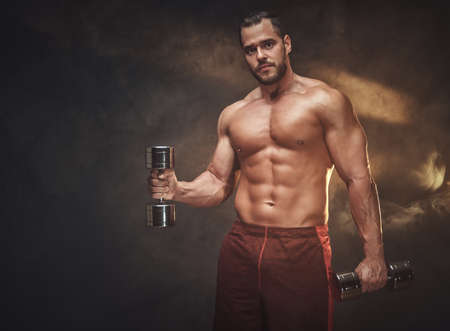 Photo for Young handsome bodybuilder is posing for photographer with dumbbells. - Royalty Free Image
