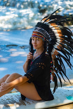 Photo pour Portrait of a half-naked tribal female model posing on an ocean shore while sitting on a surfing board, wearing long ethnic indian chief headdress made of feathers - image libre de droit