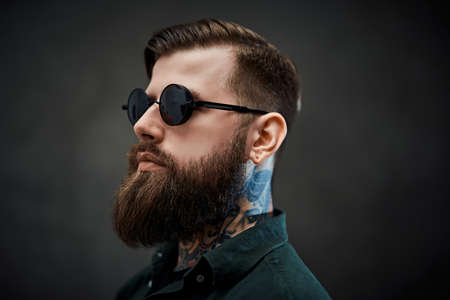 Photo for Closeup portrait of a cool bearded male in sunglasses on a dark background - Royalty Free Image
