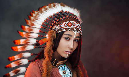 Photo pour Portrait of a beautiful American Indian woman in ethnical costume and traditional make up. Studio portrait on a dark background - image libre de droit