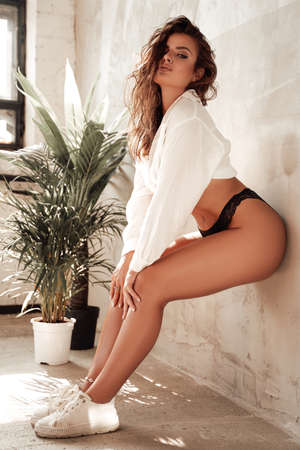 Foto de Tanned sexual woman with curly hairs in white shirt and black underwear posing near wall with plants in background. - Imagen libre de derechos