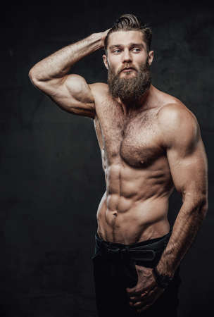 Photo for Cool and haired shirtless man with beard and moustache in pants posing with hand in pockets and hand under head in studio. - Royalty Free Image