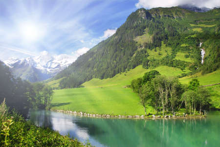 View at alpine mountain peaks from the mountain lake with a sun shining and rays