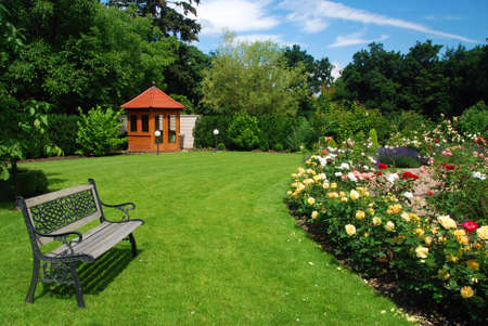 Beautiful garden with blooming roses, brick path, bench and a small gazebo