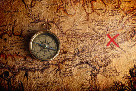 Photo pour Old brass compass lying on a very old map showing the way to treasure - image libre de droit