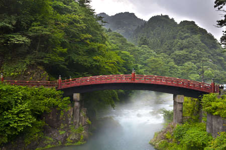 Red sacred bridge Shinkyo in Nikko, Japan and a mist rising from the river