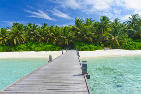 Tropical Maldivian paradise - a jetty leading to a beautiful tropical atoll hiden in the azu