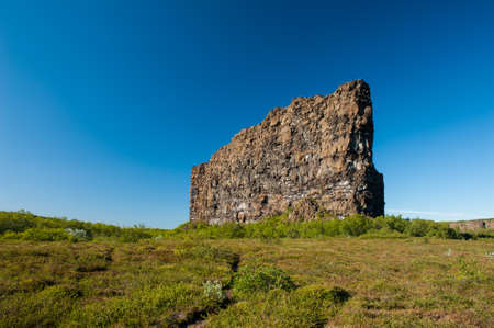 Eyjan rock in Asbyrgi. Asbyrgi is a horseshoe-shaped canyon in the national park Jokulsargljufur in the North of Iceland. The rocky walls of the canyon are up to 100 high and very steep. The canyon was probably formed during great glacial floods