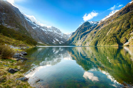 Peaks of Darran Mountains reflecting in a Lake Marian Fiordland national park New Zealand