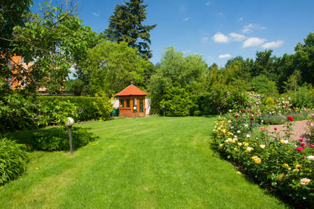 Foto de Beautiful garden with blooming roses, brick path and a small gazebo - Imagen libre de derechos