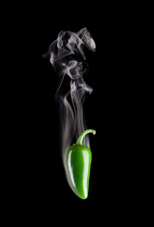 Smoking hot green jalapeno pepper (Capsicum Annuum) isolated on a pure black background.