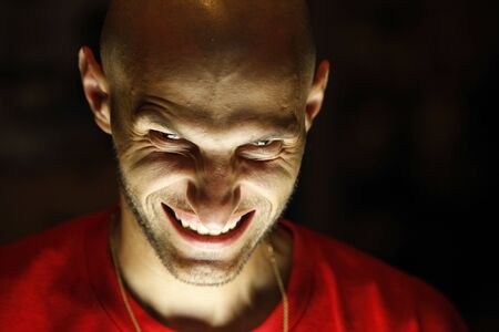 terrifying man with a grin as a smile looking at the camera with his chin down and the light under his face
