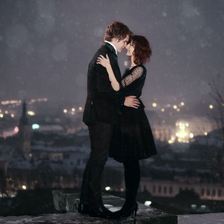 Photo pour Full length profile of Romantic Couple looking into each others eyes against the city at night on valentine's day - image libre de droit