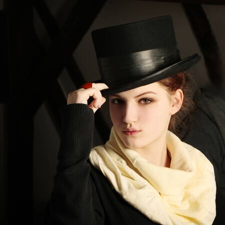 Classic young lady with black hat and beige scarf looking at the camera