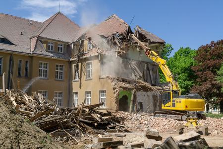 Photo pour Big yellow excavator breaks down old house at summer - image libre de droit