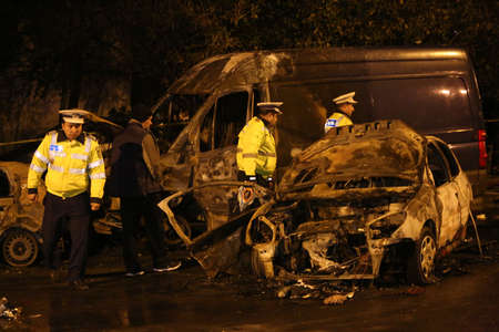 BUCHAREST, ROMANIA - November 07, 2017: Police, forensics inspect car burned after an accident. Two burnt to death when the car erupted in flames after a drunk driver hit a car and crashed.